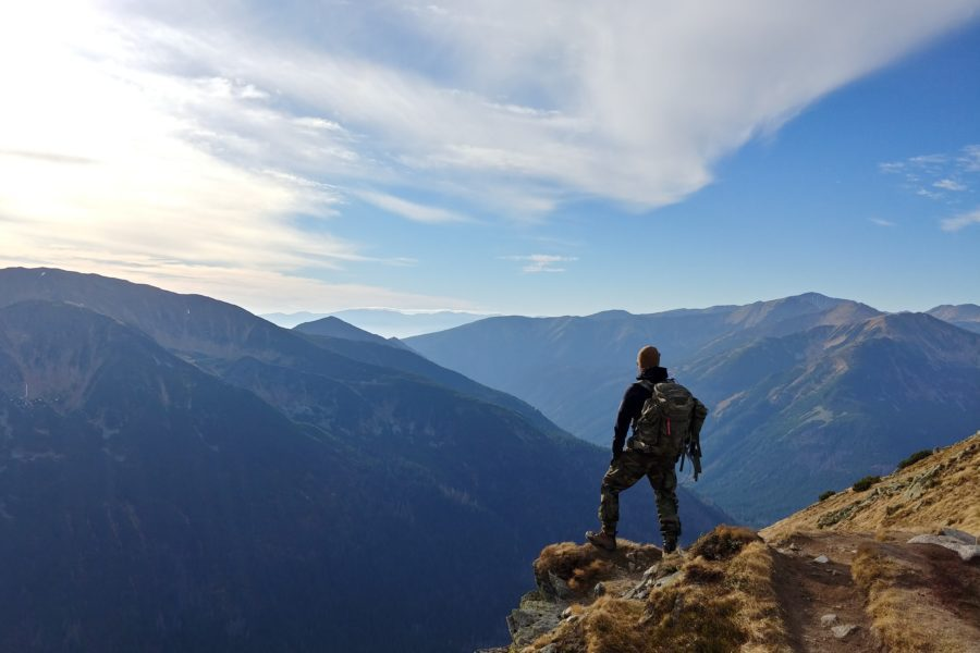 man on top of mountain under blue sky